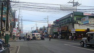 Visual pollution - Electrical and communication wires hang above an intersection in MacArthur Highway in Marilao, Bulacan, Philippines. A complex mix of commercial signs make up the view's background.