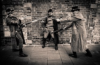 Mexican standoff - Three men pointing guns at one another in an apparent Mexican standoff