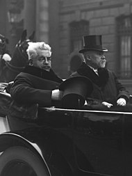 Zwart-witfoto van twee mannen die achterin een paardenkoets zitten: de linker heeft ruig grijswit haar, een donkere snor, een bril en houdt een hoed in zijn rechterhand, terwijl de rechter heeft een witte snor en een sik, en draagt een hoed op zijn hoofd;  op de achtergrond is een Republikeinse Garde te onderscheiden