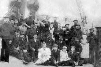 SS Mona's Isle (1882) - The crew of Mona's Isle (circa 1900). First Officer James Teare, who would later go on to become a Master of the line (and command Ellan Vannin on her ill-fated voyage), can be seen seated at the far left of the photograph. The woman in the center of the photograph is Florence Helena Cowell.