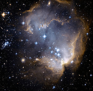 "NGC 602 and N90 as seen by Hubble Space Telescope's ACS. NGC 602 is the designation for a particular young, bright open cluster of stars located in the Small Magellanic Cloud, a satellite galaxy to our own Milky Way. Radiation and shock waves from the star cluster has pushed away much of the lighter surrounding gas and dust that compose the nebula known as N90, and this in turn has triggered new star formation in the ridges (or ""elephant trunks"") of the nebula. These even younger stars are still enshrouded in dust but are visible to the Spitzer Space Telescope at infrared wavelengths. The image spans about 200 light years, and a number of more distant galaxies also appear in the background."
