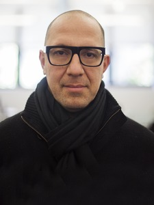 Headshot of a bald man with glasses, smirking at the camera.