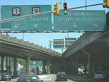 A ramp at a traffic light with a set of two overhead green signs. The one on the left reads U.S. Route 1/U.S, Route 9 north Lincoln Tunnel with two arrows pointing to the lower left and the one on the right reading Hoboken Holland Tunnel with a down arrow and an arrow pointing to the lower right.