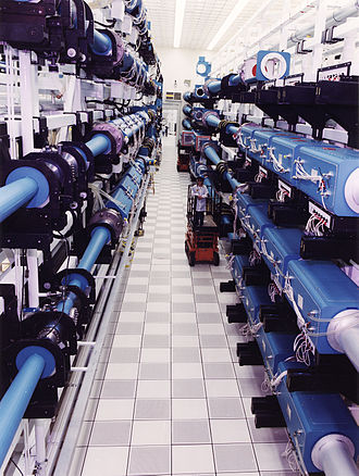 "Nova (laser) - View down Nova's laser bay between two banks of beamlines. The blue boxes contain the amplifiers and their flashtube ""pumps"", the tubes between the banks of amplifiers are the spatial  filters."