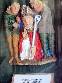 Painted statues of three men. The man in the centre is wearing a mitre and carrying a crozier and is staring straight forward. One of the two men flanking the central figure is carrying an axe.