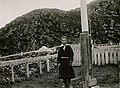 Pike i samisk drakt stående ved flaggstang foran innngjerdet hageområde. Lagget kar plassert t.h - Norsk folkemuseum - NF.13322-013.jpg