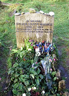 "Flowers in front of a simple headstone bearing the inscription, ""In memory Sylvia Plath Hughes 1932–1963 Even amidst fierce flames the golden lotus can be planted."""