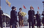 Princess Elizabeth holding flowers on stage with Prince Philip and several people. Royal Visit 1951, Ontario (2).jpg