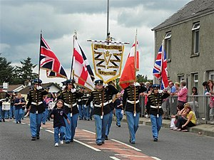 "Orange walk - The ""Red Hand Defenders"" flute band marching with the Orange Order in Newtownstewart on 12 July 2010. The flags being carried are the Union Flag, Ulster Banner and Boyntandard"