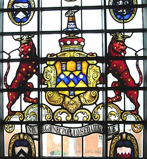 "John Rolle, 1st Baron Rolle - Heraldic achievement of Lord Rolle (died 1842) in first-floor window at top of grand staircase, Bicton House. Motto: Nec Reg(in)a Nec Populo Sed Utroque (""Not with the Queen, not with the People, but with each""). Arms: Or, on a fesse indented azure between three billets of the second each charged with a lion rampant of the first three bezants. The canting crest is a dexter cubit arm holding in the hand a roll of parchment, the crests of earlier family members hold a baton (Chittlehampton Church) or a flint-stone (Library Room, Stevenstone). Sable, a chevron between three hands grasping a stone argent were the canting arms of the mediaeval de Stevenstone family of Stevenstone"
