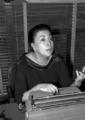 Rosario Castellanos conversa sentada tras un escritorio, retrato.png