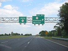 A four lane freeway at an interchange. Two green overhead signs stand over the road with the left one reading south Route 55 and the right one reading exit 27 Route 47 Vineland Millville with an arrow pointing to the upper right