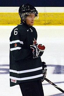A teenage ice hockey player standing relaxed on the ice. He wears a green jersey with white trim and a black, visored helmet.