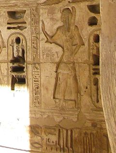 Relief of a man standing, surrounded by hieroglyphs.