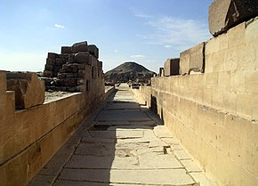 A photo taken from inside the causeway facing the direction of the pyramid. Much of the walls is missing, though what remains is in good condition. The pavement is damaged though generally intact. The pyramid can be seen far into the distance.
