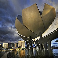 "A lotus-inspired building designed by Moshie Safdie that features 10 ""fingers"" anchored by a unique round base in the middle."