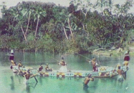 Solomon Island warriors, armed with spears, on board an ornamented war canoe (1895)