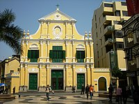 The facade of a yellow baroque-style church