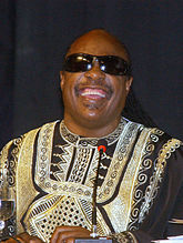 A man smiling, wearing black sunglasses and colorful clothing, behind a microphone.