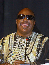 Older man smiling and wearing black sunglasses while in front of a microphone.