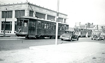 Two streetcars passing on a wide street