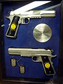 "A case with two handguns, both with a stamped Smiley Face - one of the guns has ""To Edward Blake, With Gratitude"" around the Smiley, while the other has ""Richard Nixon - 1976"" -, dogtags, and a circular plaque, written by Richard Nixon, stating they are a gift to the Comedian in recognition for his services."