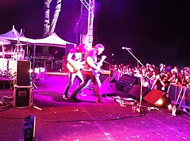 Side of stage shot of a band playing. Two members are shown in right profile both are playing guitars. Other stage equipment is visible around them. The audience is to the right and below stage level.