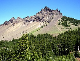 A jagged mountain with spires rises above its lightly forested slope, with a more heavily forested area in the foreground of the picture.