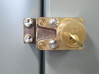 Trapped key interlocking - This is a trapped key interlock on the door of an electrical switchgear cabinet. It is attached with one-way security screws to discourage casual removal, which would defeat the interlock scheme.