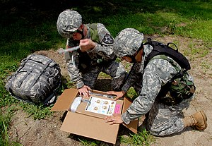 B-ration - UGR-Express. The soldiers depicted are activating the included heating unit by pulling the tab(s)
