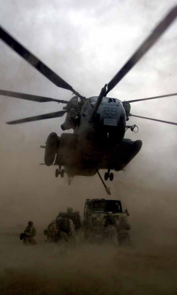 US Navy 030224-M-4066S-009 A CH-53 Sea Stallion helicopter hovers over a British military vehicle