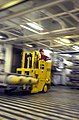 US Navy 030324-N-1974E-001 Aviation Ordnanceman 3rd Class Joshua Young from Cincinnati, Ohio, uses a forklift to move 1,000-lb. bombs in one of the weapons magazines aboard the aircraft carrier USS Nimitz (CVN 68).jpg
