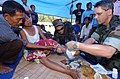 US Navy 050425-N-7027P-186 Lt. Cmdr. Eric Kasowski, left, along with U.S. Public Health Services Capt. David Rutstien, right, provide medical assistance to an Indonesian woman.jpg