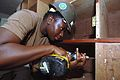 US Navy 051226-N-4374S-012 Store Keeper 2nd Class Sparkole Dyeth, a U.S. Navy Seabee assigned to Naval Mobile Construction Battalion Three (NMCB-3), helps refurbish a wooden cabinet.jpg