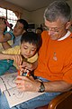 US Navy 060624-N-5334H-092 Seventh Fleet Chaplain, Capt. Bill Devine helps a child with his coloring book during a community service project at the Jinhae Jae-Hual-Won Orphanage for Handicapped Children.jpg