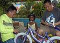 US Navy 070713-N-4021H-118 Senior Chief Electrician's Mate Arnold Salido and Chief Personnel Specialist Edward Lopez, of USS Pearl Harbor (LSD 52), assemble bicycles for children while delivering Project Handclasp materials to.jpg