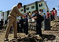 US Navy 090220-N-3262C-274 Cryptologic Technician (Collection) 1st Class Nicole Duran hands off debris to Capt. James Puttler, U.S. 7th Fleet chaplain, while clearing a lot for the construction of a playground.jpg
