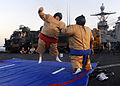US Navy 090919-N-5345W-088 Ship's Chaplain Lt. Stephen Warne sumo wrestles with Boatswain's Mate 2nd Class Austen Gant during a steel beach picnic aboard the amphibious dock landing ship USS Fort McHenry (LSD 43).jpg