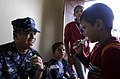 US Navy 100719-N-9643W-219 Lt. Michael Quisao plays the kazoo with a student from Escuela De Las Pampas during a community relations event.jpg