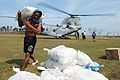US Navy 101022-N-8014S-072 Philippine citizens, government volunteers and members of the Philippine Armed Forces unload bags of rice, water and sup.jpg