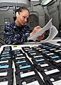 US Navy 110425-N-DM338-059 Hopsital Corpsman 1st Class Angela Kennedy, from Wendover, Utah, screens the names of Sailors who have turned in their T.jpg