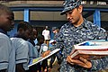 US Navy 120216-N-IZ292-045 Seaman Thomas Bailey, assigned to the guided-missile frigate USS Simpson (FFG 56), hands books to school children from t.jpg