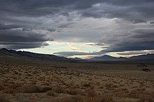 Eine Landschaftsaufnahme eines langen, trockenen Tals.  Der Himmel ist teilweise bewölkt, aber der blaue Himmel bricht in Flecken durch.  Es ist ein Schaufenster von Nevadas natürlicher Schönheit.