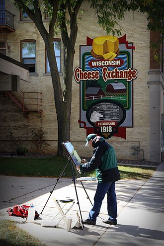 Plymouth, Wisconsin - An artist works on his canvas next to one of the Walldogs murals that dot downtown Plymouth.