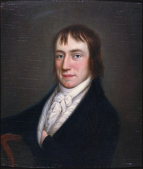 Half length portrait of rosy-cheeked man in his late twenties, sitting in black coat and white high-necked ruffled shirt with his left hand in his coat. He has medium-length brown hair.
