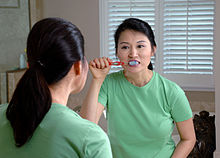 An Asian woman brushing her teeth while looking in a mirror.