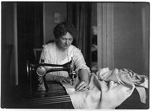 English: Woman sewing on old treadle machine