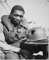 """Coast Guardsman Charles Tyner, Fireman first class, examines the jagged shrapnel hole in the helmet he wore during the - NARA - 513183.tif"
