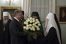 Filaret and Poroshenko, holding a bouquet of white roses