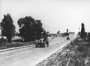 An open-topped sports car, with '3A' written on the front, kicks up dust as it drives along a road lined with trees and grass. Another open-topped sports car trails behind.
